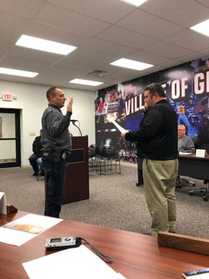 Gibsonburg Mayor Steve Fought, right, swears in new police chief Dan Collins.