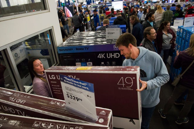 Black Friday shopping will look nothing like the past few years. This year, COVID-19 is turning Thanksgiving and Black Friday shopping on its head. More consumers are opting for online shopping with free delivery or picking up at the store. Customers Katie Webber and Cody Limmer carry a Black Friday discounted television in this 2018 file photo taken at Best Buy in Fort Collins, Colo.