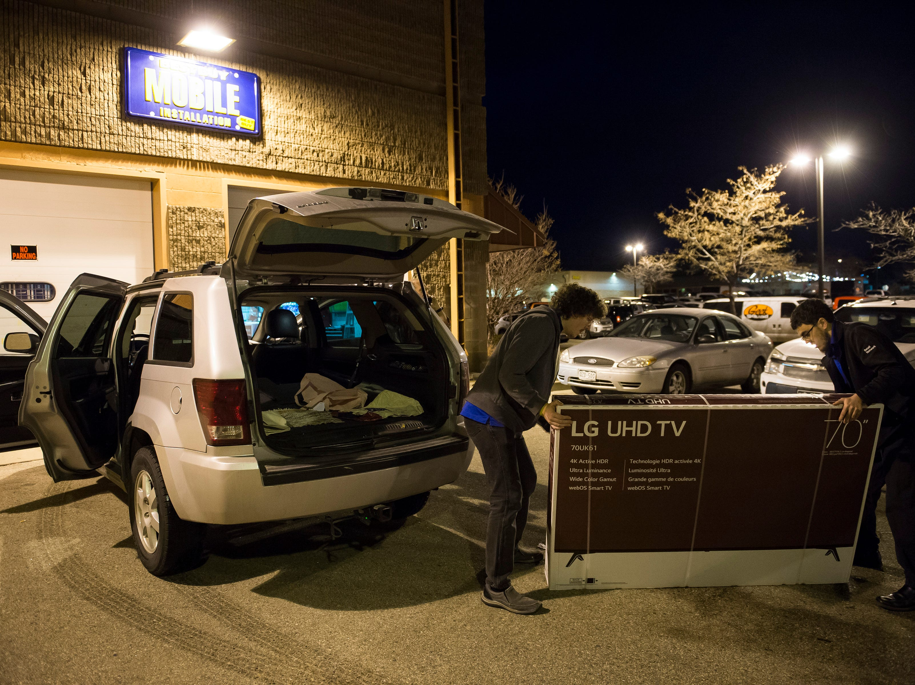 Best Buy employees Jacob Gentrup, left, and Sam Field load up large televisions into customer vehicle on Thursday, Nov. 22, 2018, at Best Buy in Fort Collins, Colo.