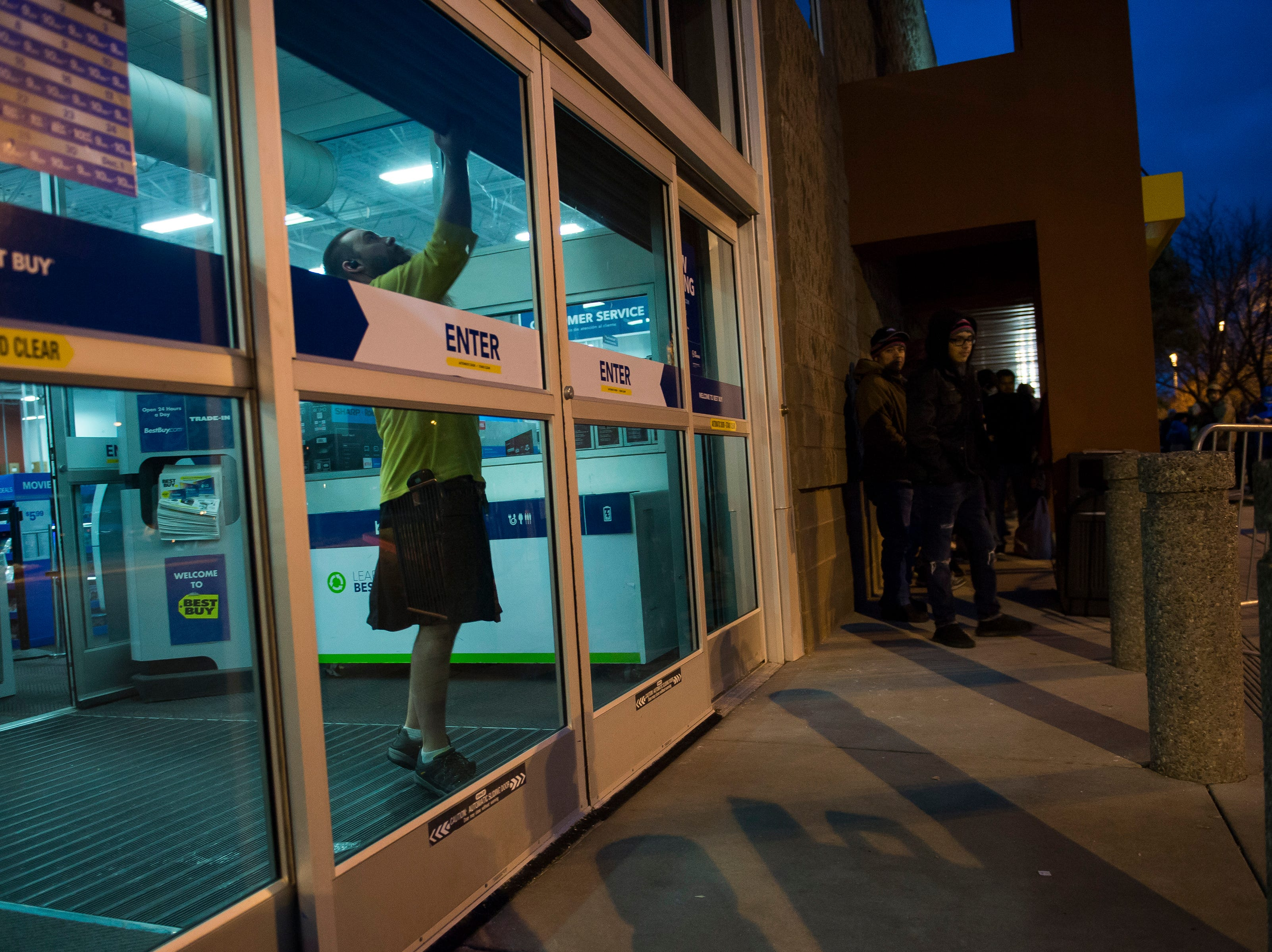 Head of security Travis Neal lifts up the security shutters before letting customers in on Thursday, Nov. 22, 2018, at Best Buy in Fort Collins, Colo.