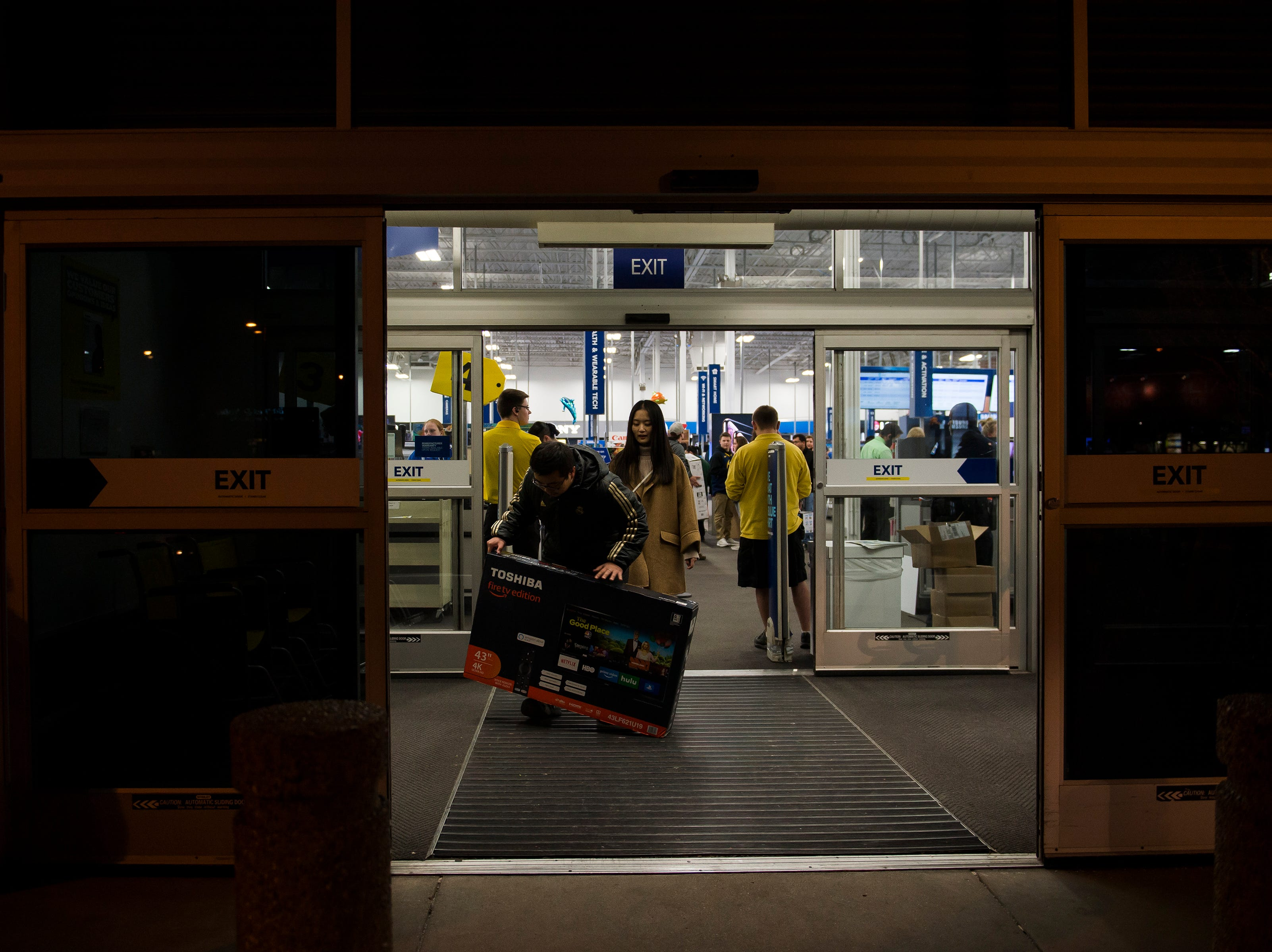 Customers make their way outside after purchasing a television on Thursday, Nov. 22, 2018, at Best Buy in Fort Collins, Colo.