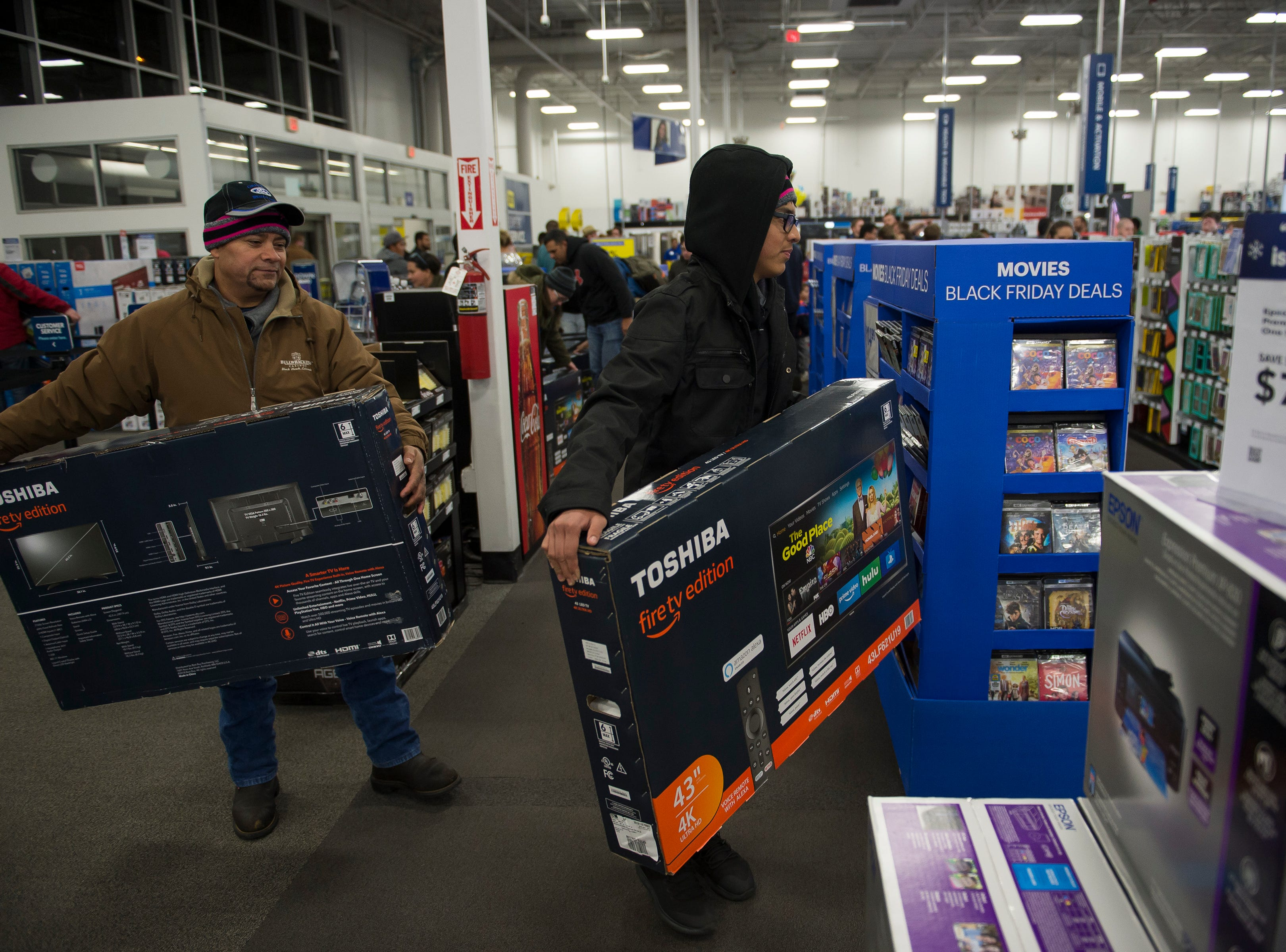 Father and son Jose and Saul Castaneda grab their door-buster deal televisions on Thursday, Nov. 22, 2018, at Best Buy in Fort Collins, Colo. The Castaneda came from Greeley and had been waiting in line outside Best Buy since about 7 a.m.