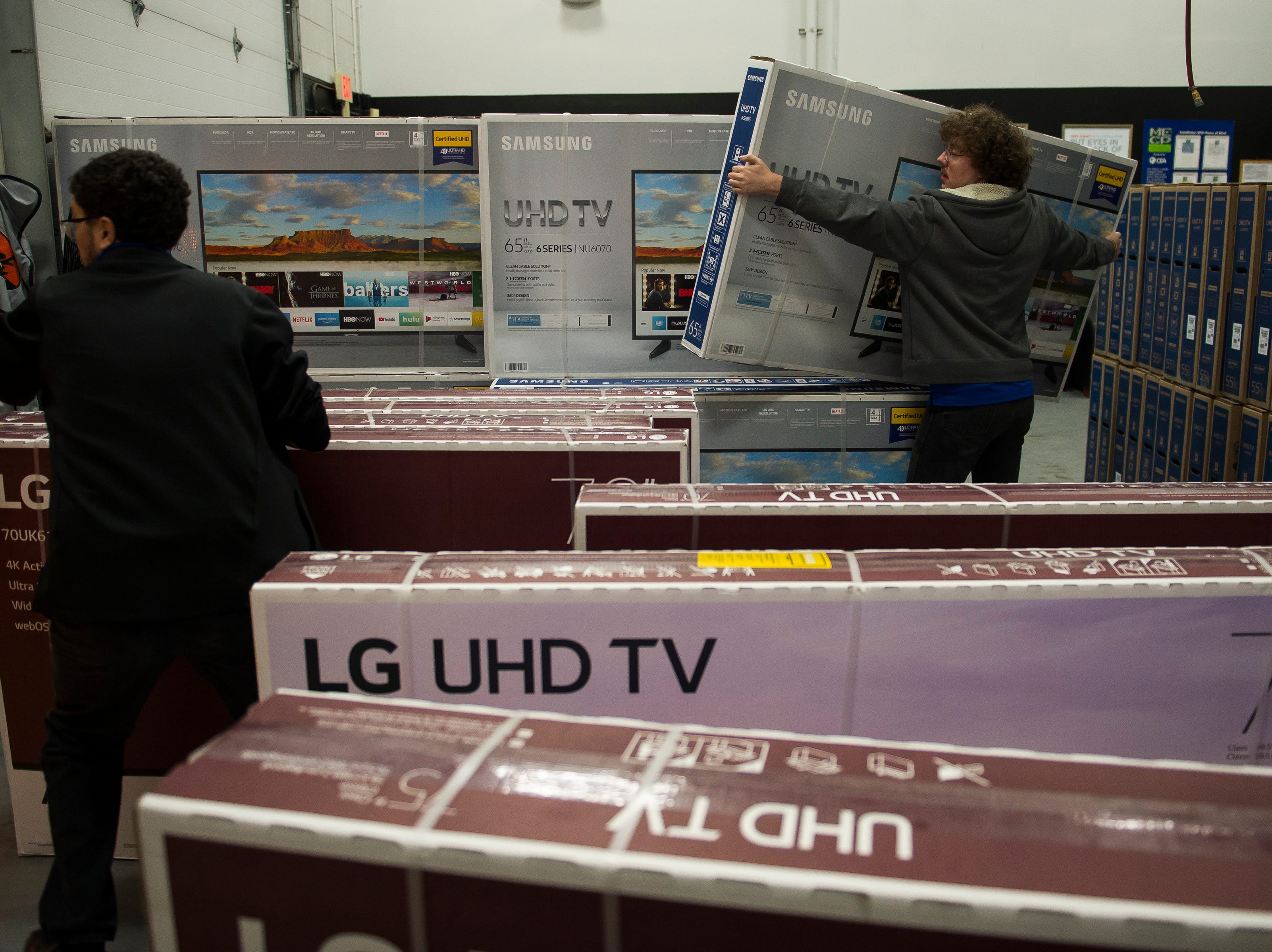 Best Buy employees Jacob Gentrup, right, and Sam Field load up large televisions into customer vehicle on Thursday, Nov. 22, 2018, at Best Buy in Fort Collins, Colo.