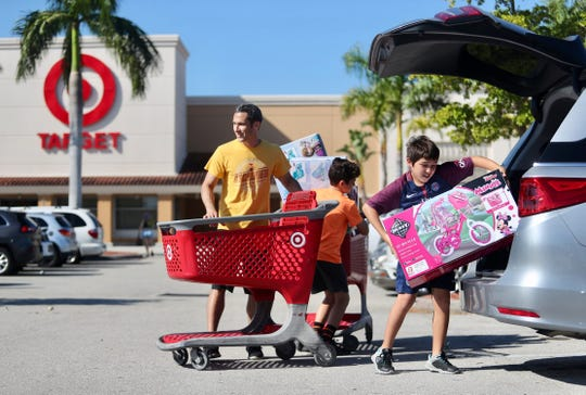 Jason Belfer and his sons Riley Belfer, 12, center, and Brady Belfer, 11, load their van at Target at The Forum in Fort Myers on Friday, Nov. 23, 2018.