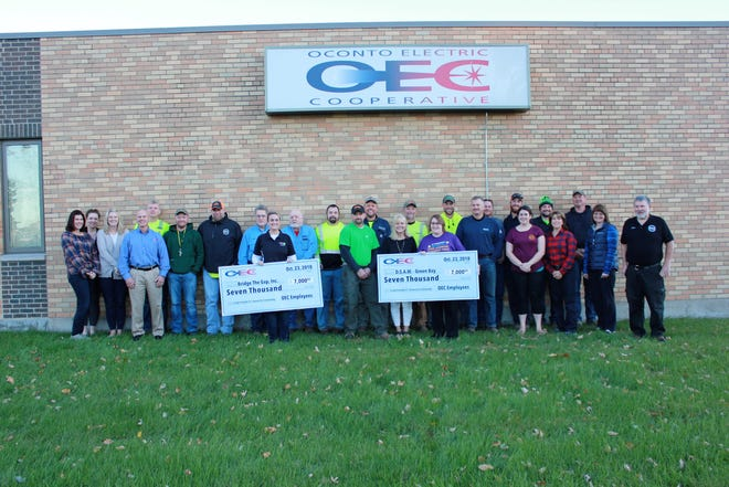 "Employees of Oconto Electric hold large ""checks"" to signify donations to two organizations last month."