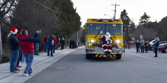 "Fired up for Santa Claus? In Baileys Harbor, the Man in the Red Suit waves as he arrives via fire truck at the front of last year's parade during the town's ""Harbor Holiday"" celebration. Santa plans to arrive the same way during this year's parade on Dec. 1"