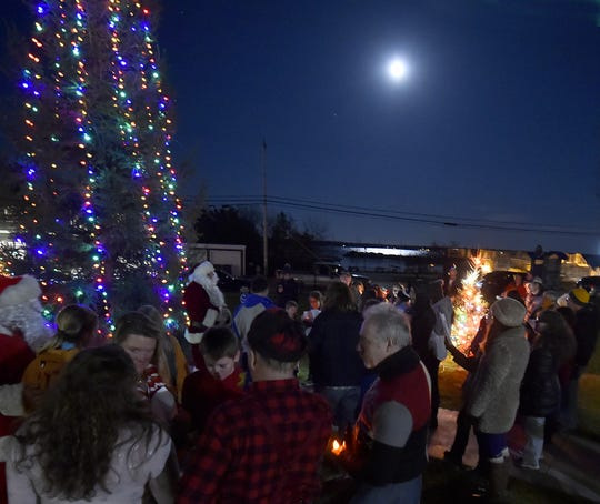 """The moon shines over Lake Michigan and the Christmas tree outside Baileys Harbor Town Hall at last year's """"Harbor Holiday"""" celebration."""