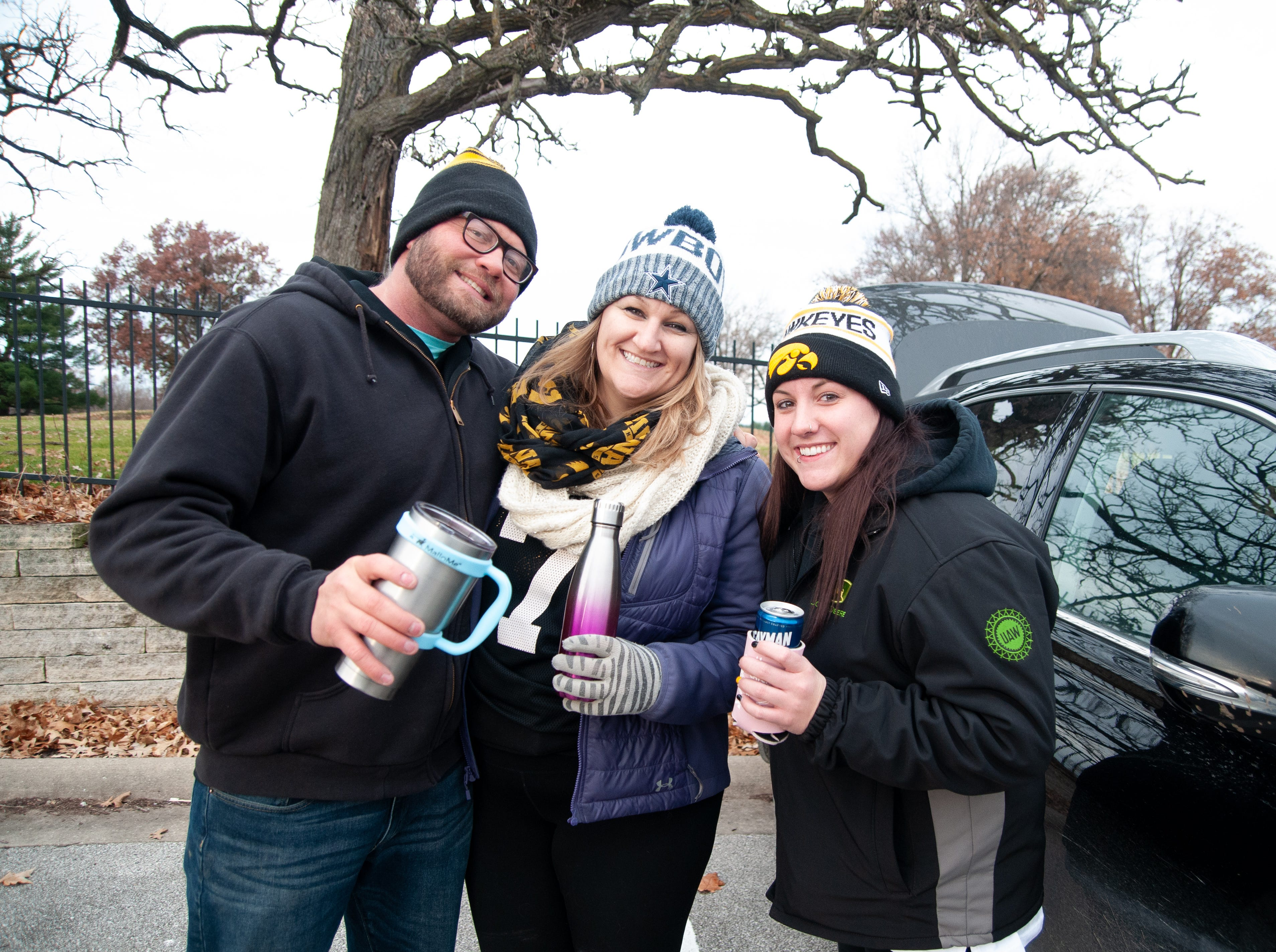 Chad Geiken, left, Elizabeth O'Connell and Jennifer Gibbs, of Waterloo, Friday, Nov. 23, 2018, while tailgating before the Iowa game against Nebraska in Iowa City.