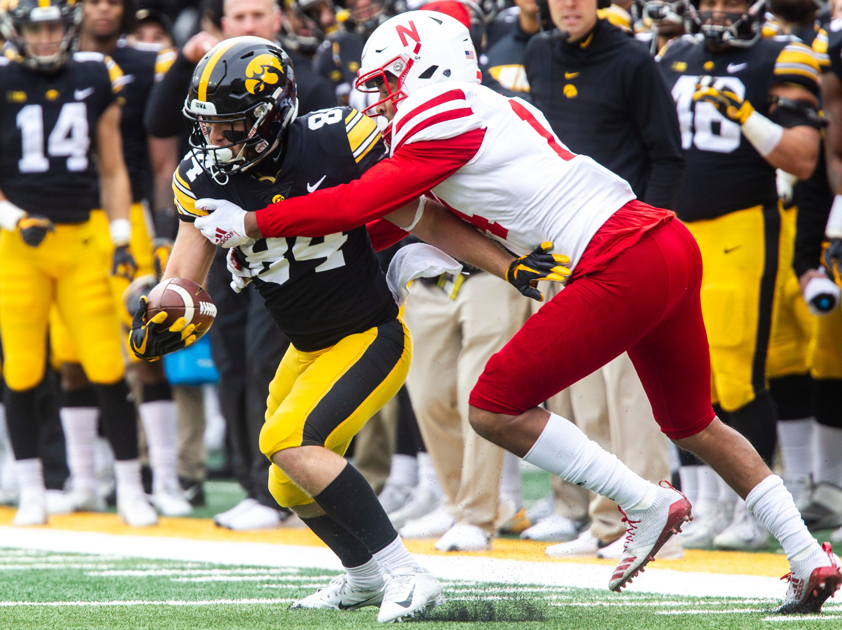 Iowa wide receiver Nick Easley (84) gets tackled by Nebraska's Tre Neal (14) during a Big Ten Conference NCAA football game on Friday, Nov. 23, 2018, at Kinnick Stadium in Iowa City.