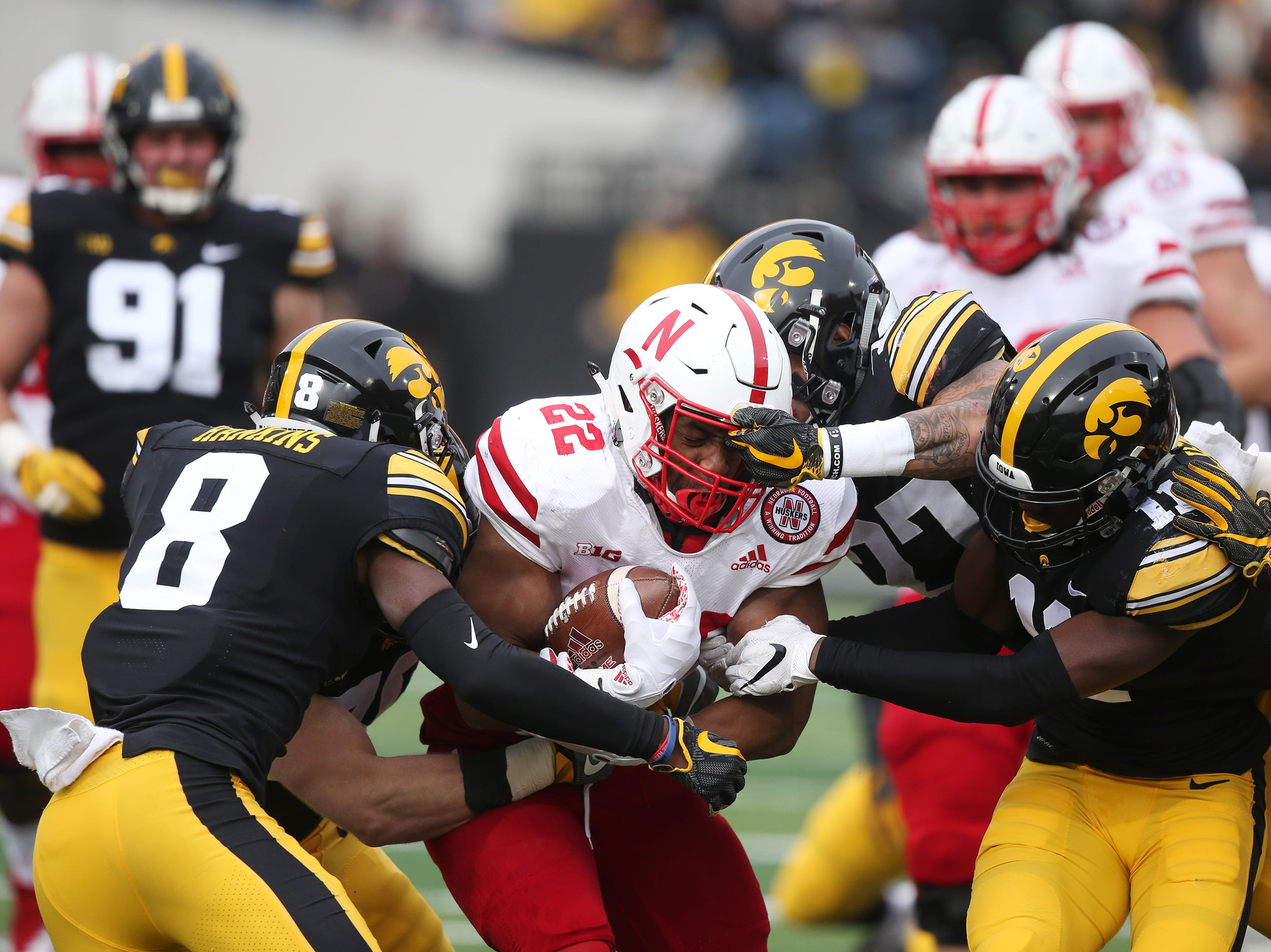 Nebraska's David Ozigbo is brought down by Iowa's Matt Hankins (8) Amani Hooker (27) and Michael Ojemudia (11) during the senior day match-up between the Iowa Hawkeyes and the Nebraska Cornhuskers on Friday, Nov. 23, 2018, at Kinnick Stadium, in Iowa City.