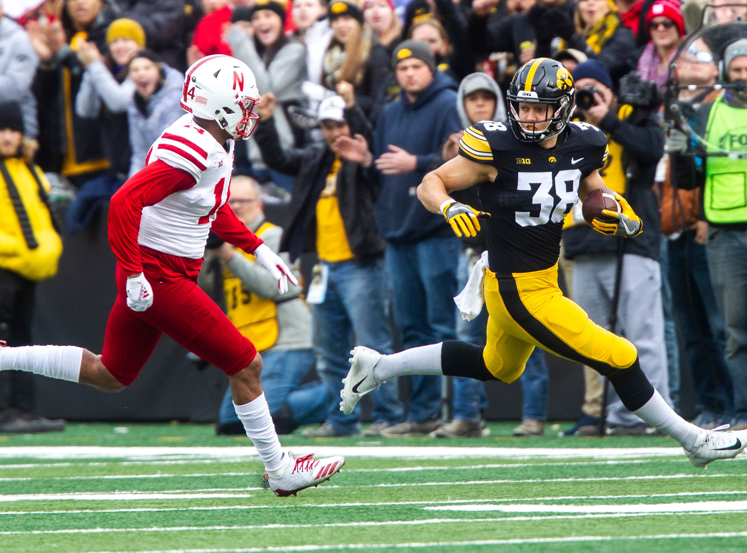 Iowa tight end T.J. Hockenson (38) evades Nebraska's Tre Neal (14) on a 25-yard reception during a Big Ten Conference NCAA football game on Friday, Nov. 23, 2018, at Kinnick Stadium in Iowa City.