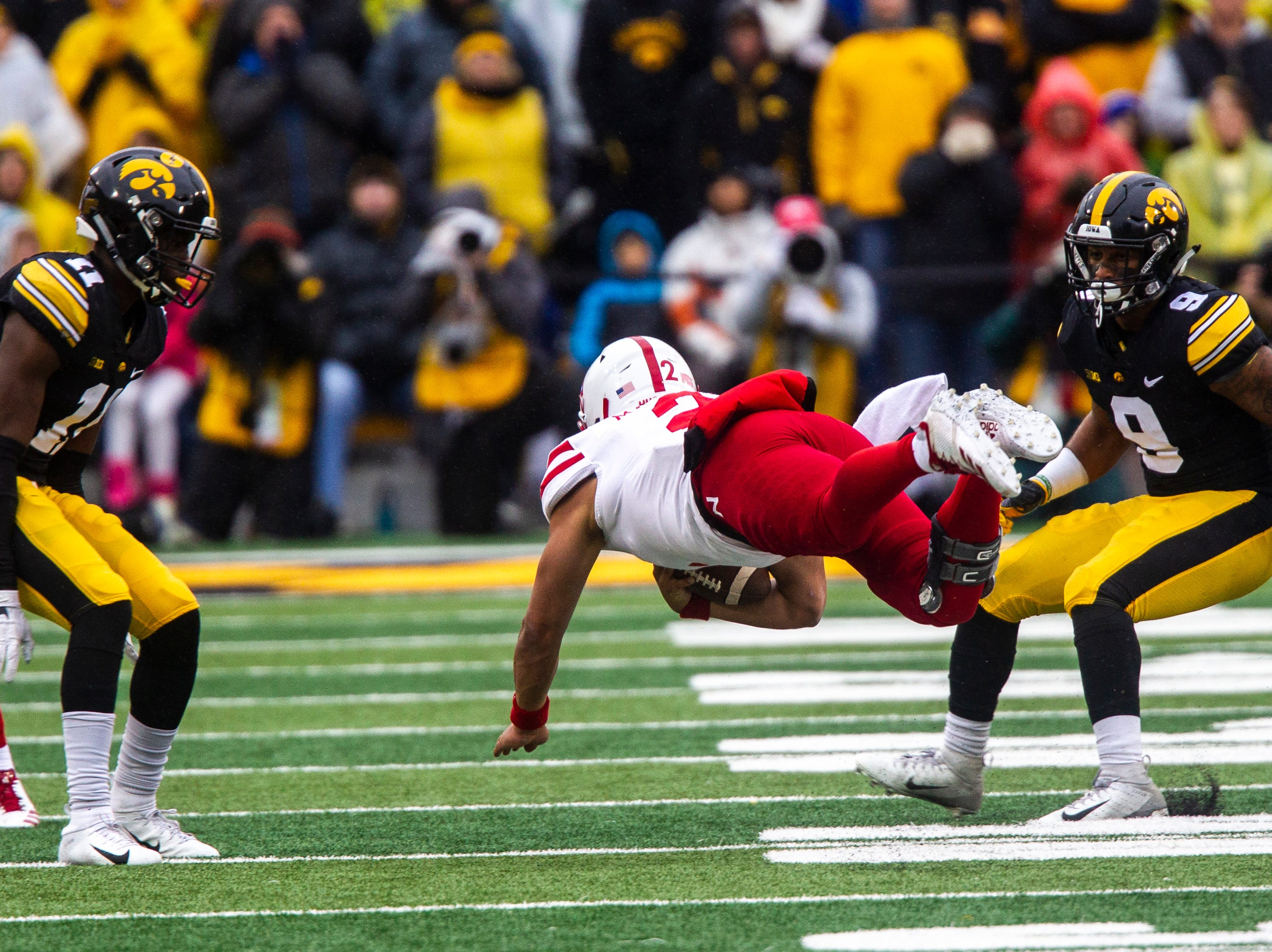 Nebraska quarterback Adrian Martinez (2) dives to avoid tackles from Iowa defensive back Michael Ojemudia (left) and Iowa defensive back Geno Stone (right) during a Big Ten Conference NCAA football game on Friday, Nov. 23, 2018, at Kinnick Stadium in Iowa City.