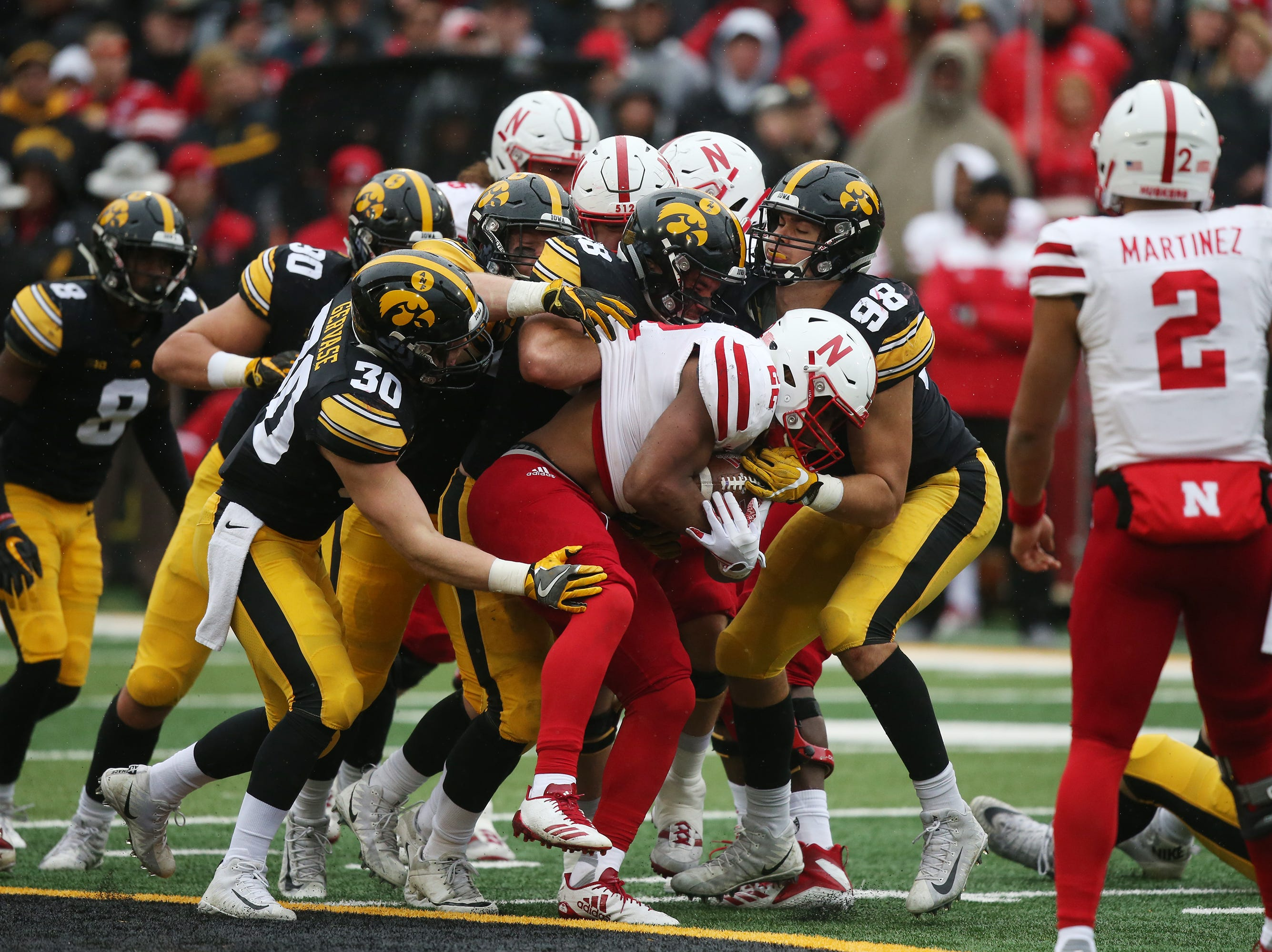 Iowa's Jake Gervase (30) Parker Hesse (40) Jack Hockaday (48) and Anthony Nelson (98) bring down Nebraska's Devine Ozigbo during the senior day match-up between the Iowa Hawkeyes and the Nebraska Cornhuskers on Friday, Nov. 23, 2018, at Kinnick Stadium, in Iowa City.