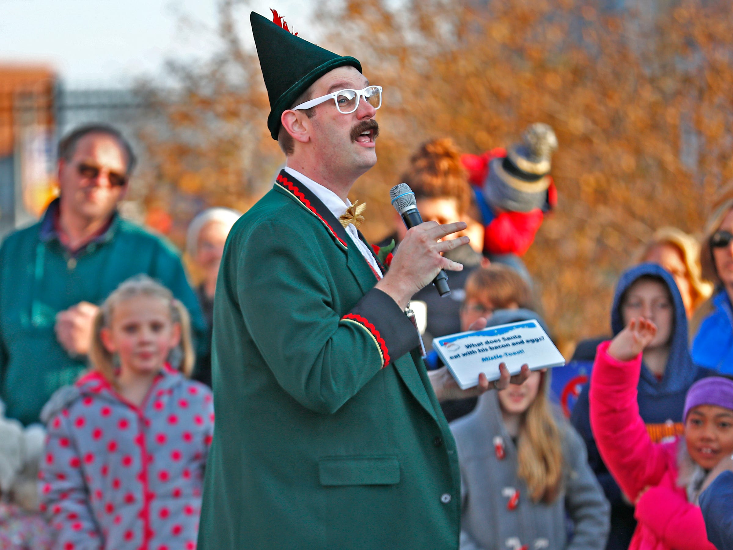 Zazzelz, the Elf, aka Michael Hosp, tells holiday jokes to entertain the crowd as they await Santa's arrival at the Children's Museum of Indianapolis in an IndyCar driven by racer Ed Carpenter, Friday, Nov. 23, 2018.
