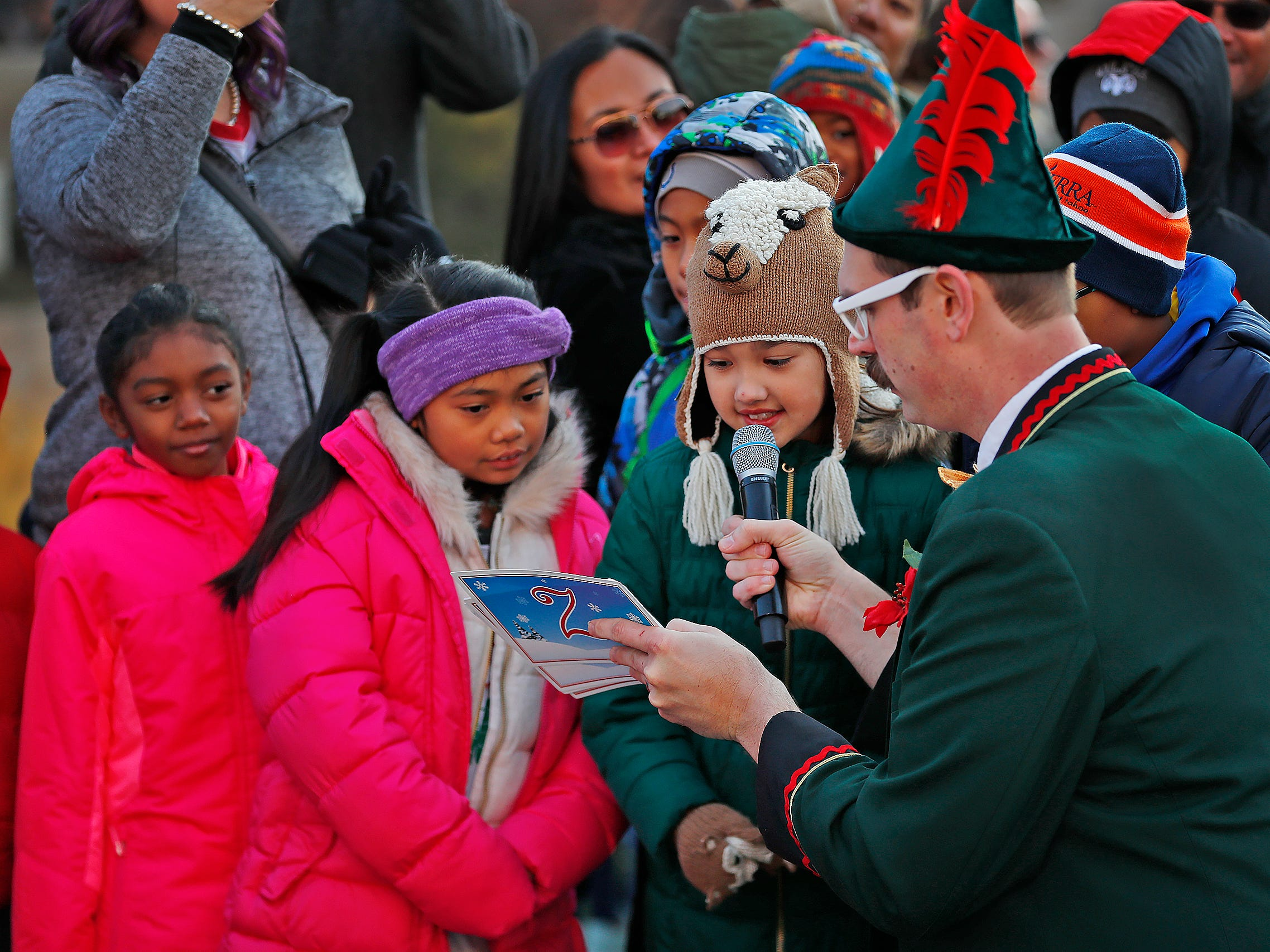Zazzelz, the Elf, right, aka Michael Hosp, gets help from kids as they tell jokes while awaiting Santa's arrival at the Children's Museum of Indianapolis in an IndyCar driven by racer Ed Carpenter, Friday, Nov. 23, 2018.