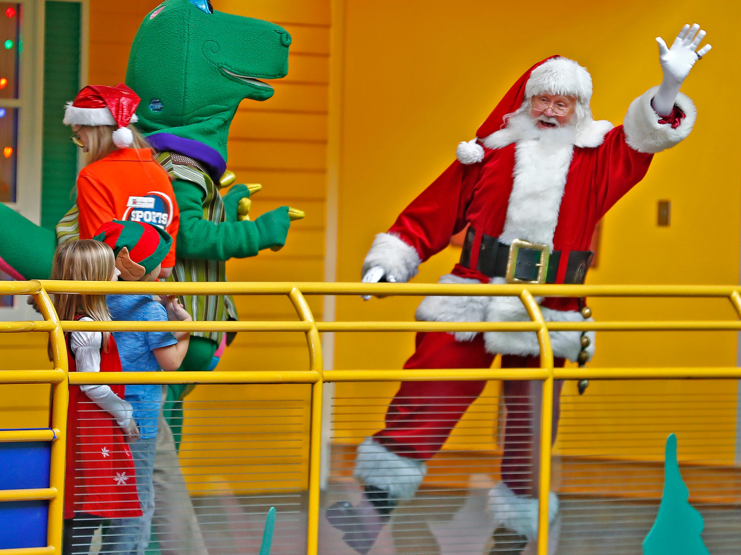 Santa waves to everyone at the Children's Museum of Indianapolis in an IndyCar driven by racer Ed Carpenter, Friday, Nov. 23, 2018.
