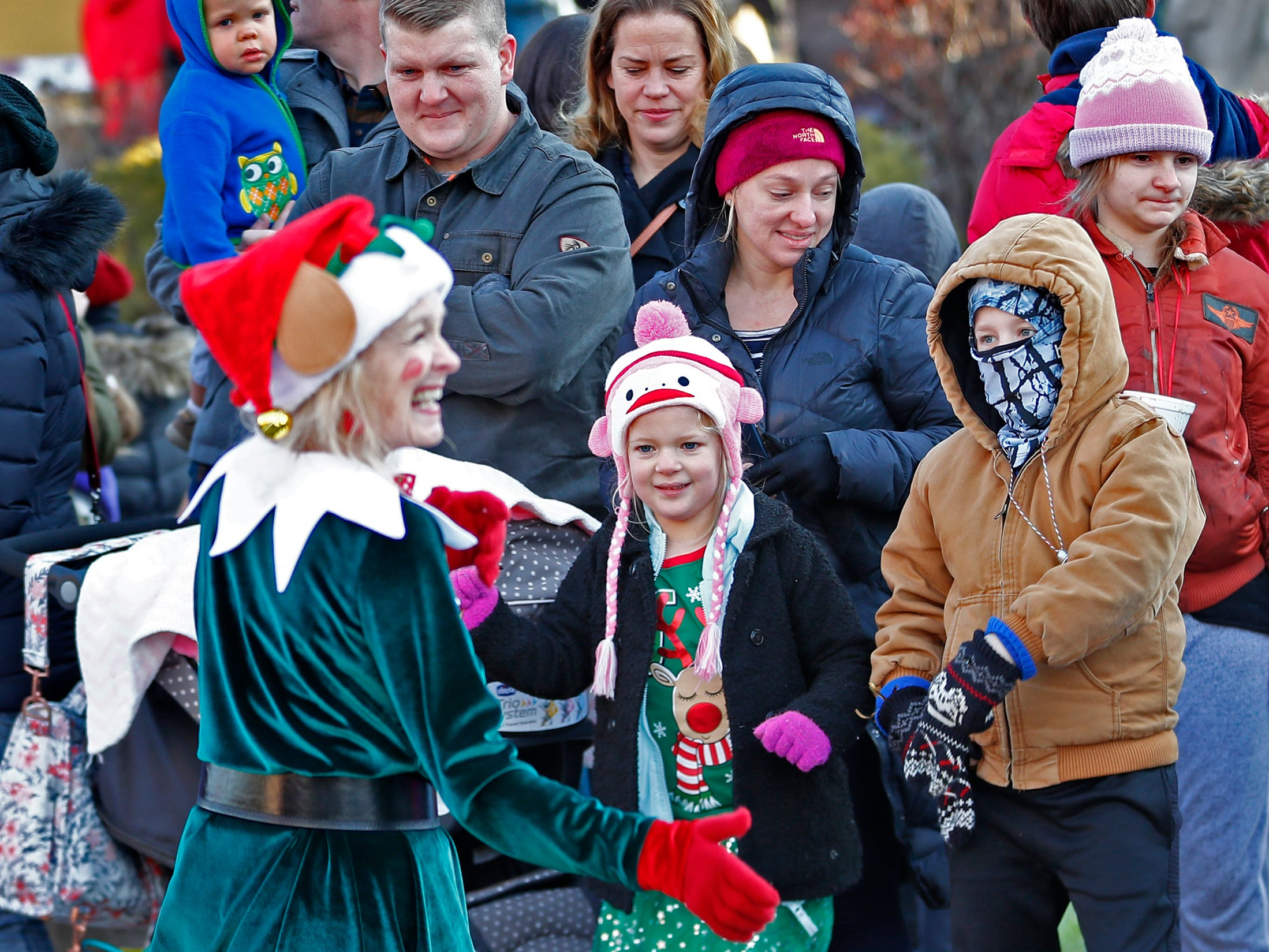 Elves entertain the crowd as everyone awaits Santa's arrival at the Children's Museum of Indianapolis in an IndyCar driven by racer Ed Carpenter, Friday, Nov. 23, 2018.  Emma Booher, center, and her brother, Ethan Booher, dance with the elves and holiday music.