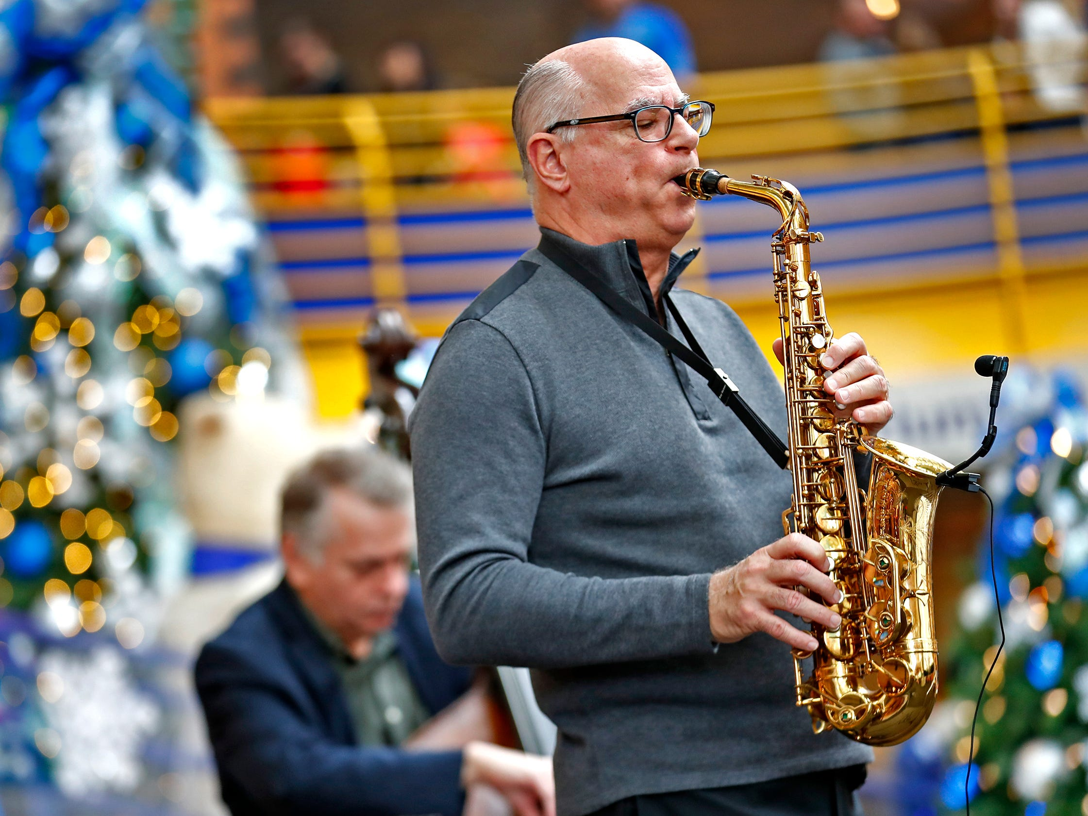 Children's Museum of Indianapolis President and CEO Jeff Patchen plays the saxophone with his group, Jeff Patchen and the Ken Fary Trio, during the opening ceremony for Jolly Days Winter Wonderland at the Museum, Friday, Nov. 23, 2018.