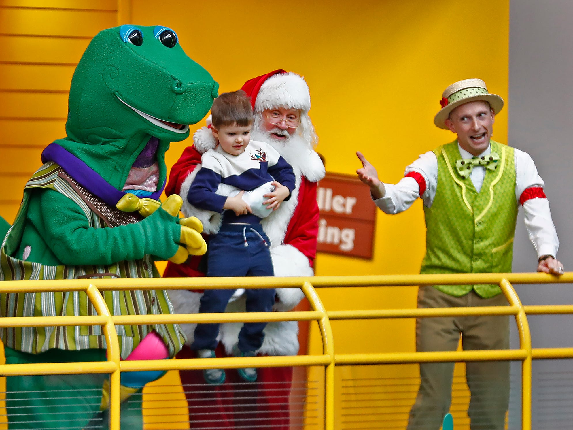 Santa, holding four-year-old Henri Duval, gets ready to slide down the Yule Slide at the Children's Museum of Indianapolis, Friday, Nov. 23, 2018. Chorduroys' leader Matt Anderson, right, introduces them, along with the museum mascot, Rex.
