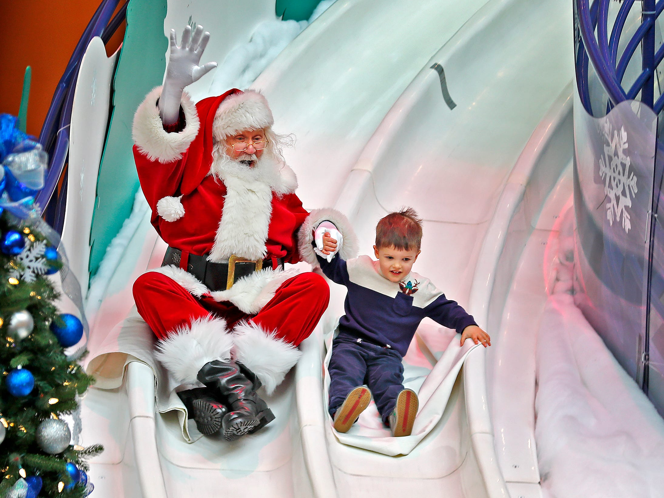 Santa and four-year-old Henri Duval slide down the Yule Slide at the Children's Museum of Indianapolis, Friday, Nov. 23, 2018, marking the opening of Jolly Days Winter Wonderland at the museum.