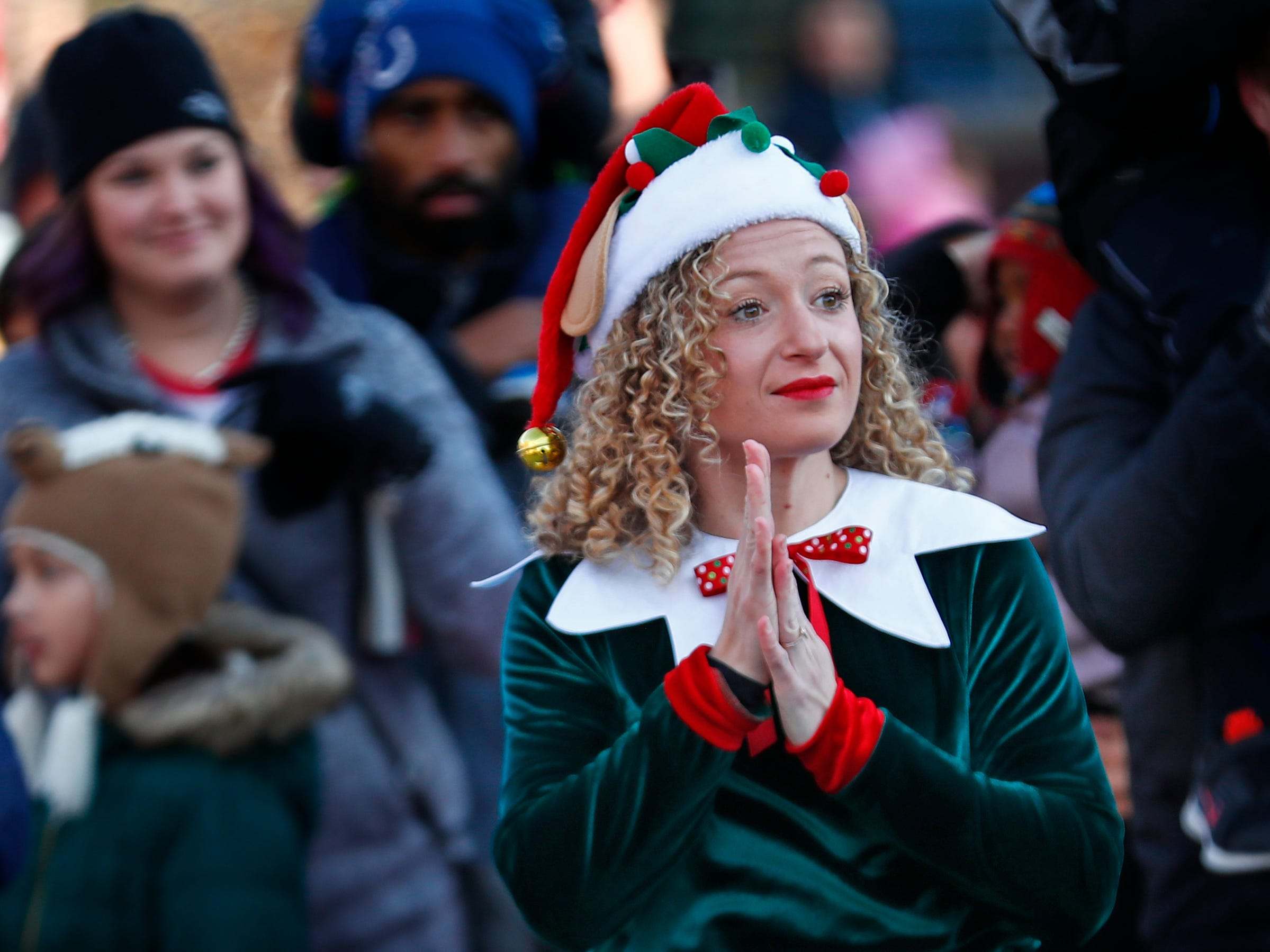 Elves, including Erika Howse entertain as the crowd awaits Santa's arrival at the Children's Museum of Indianapolis in an IndyCar driven by racer Ed Carpenter, Friday, Nov. 23, 2018.