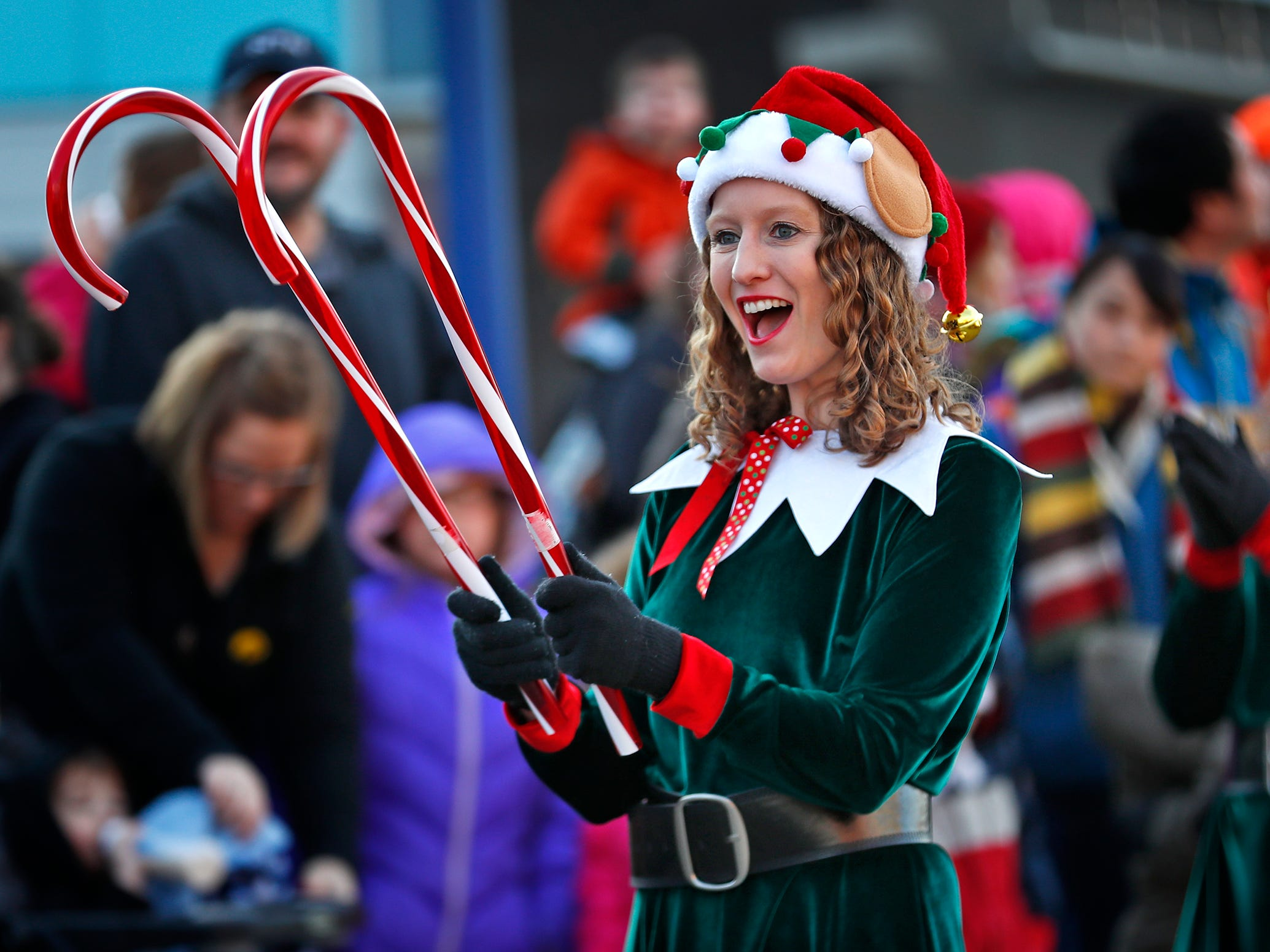 Elves, including Jenny Holland. entertain as the crowd awaits Santa's arrival at the Children's Museum of Indianapolis in an IndyCar driven by racer Ed Carpenter, Friday, Nov. 23, 2018.