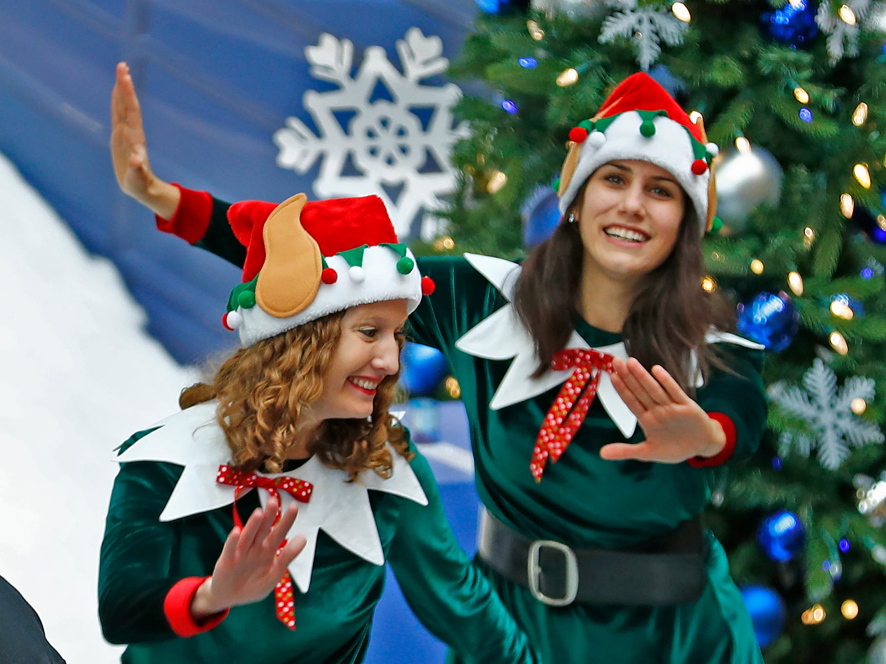 Elves Jenny Holland and Mary Malooley dance at the base of the Yule Slide, during the start of Jolly Days Winter Wonderland at the Children's Museum of Indianapolis, Friday, Nov. 23, 2018.