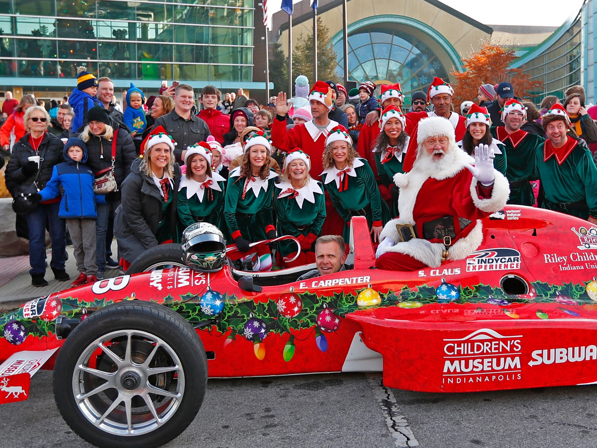 Santa poses for photos after he arrived at the Children's Museum of Indianapolis in an IndyCar driven by racer Ed Carpenter, Friday, Nov. 23, 2018.