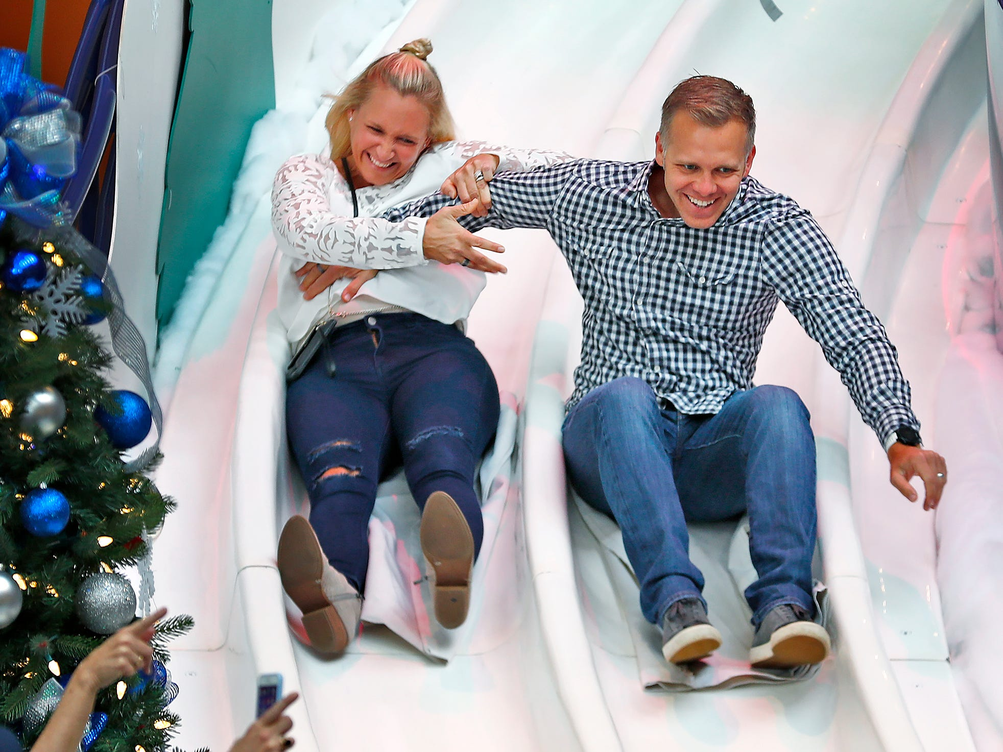 Heather and Ed Carpenter joke around as they slide down the Yule Slide at the opening of Jolly Days Winter Wonderland, at the Children's Museum of Indianapolis, Friday, Nov. 23, 2018.  Santa arrived at the Children's Museum earlier, in an IndyCar driven by racer Ed Carpenter, Friday, Nov. 23, 2018.