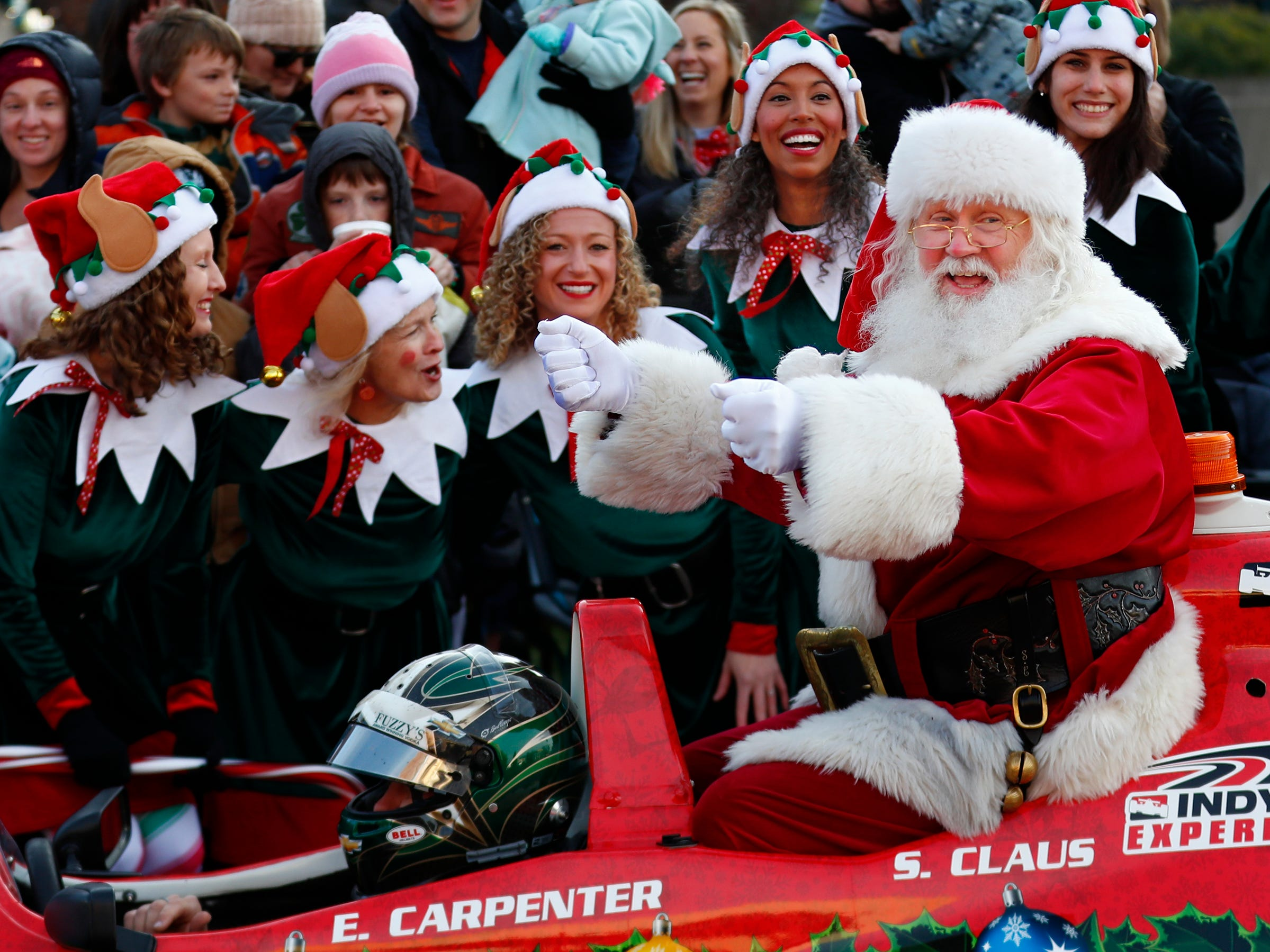 Santa poses for photos after he arrives at the Children's Museum of Indianapolis in an IndyCar driven by racer Ed Carpenter, Friday, Nov. 23, 2018.