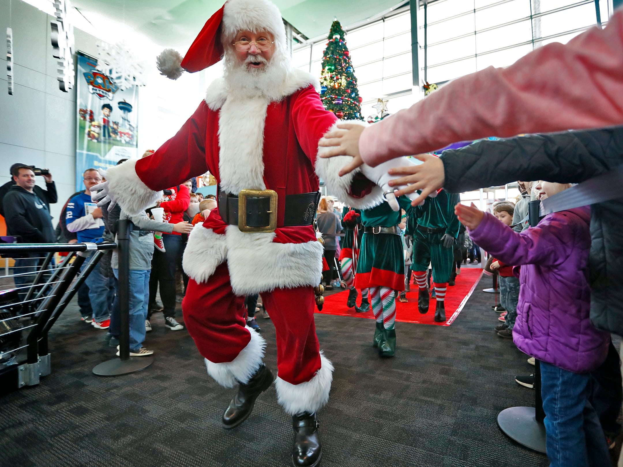 Santa greets the crowd after he arrived at the Children's Museum of Indianapolis in an IndyCar driven by racer Ed Carpenter, Friday, Nov. 23, 2018.