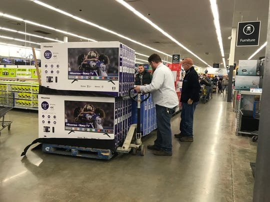 Walmart employees bring out another pallet of televisions mid-Friday morning.