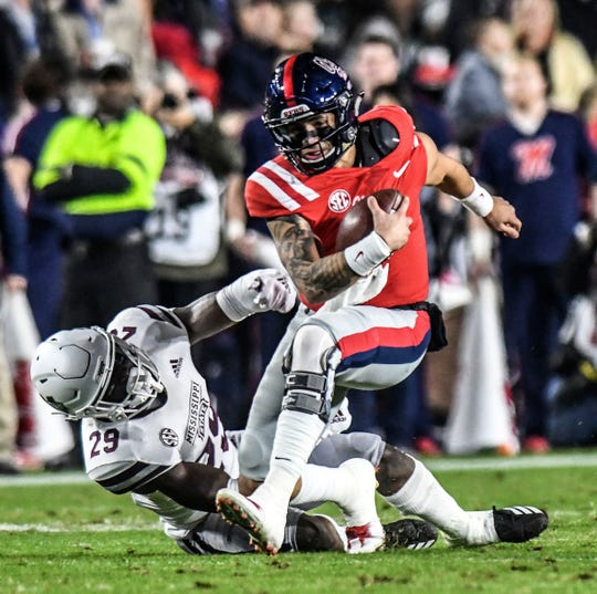 Ole Miss quarterback Matt Corral runs through a tackle by Mississippi State safety C.J. Morgan (29) during an NCAA college football game in Oxford, Miss., Thursday, Nov. 22, 2018.
