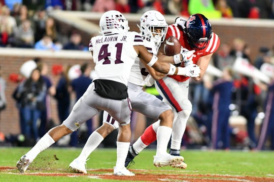 Mississippi State Bulldogs safety Mark McLaurin (41) and safety Johnathan Abram (38) attempt to tackle Ole Miss Rebels tight end Dawson Knox (9) during the first quarter of the 2018 Egg Bowl. McLaurin, Abram and Knox have all been invited to the NFL Scouting Combine.
