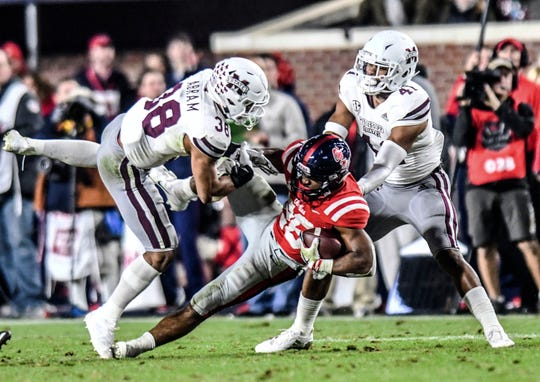 Mississippi running back Isaiah Woullard (26) is tackled by Mississippi State safety Johnathan Abram (38) and safety Mark McLaurin (41) during an NCAA college football game in Oxford, Miss., Thursday, Nov. 22, 2018.