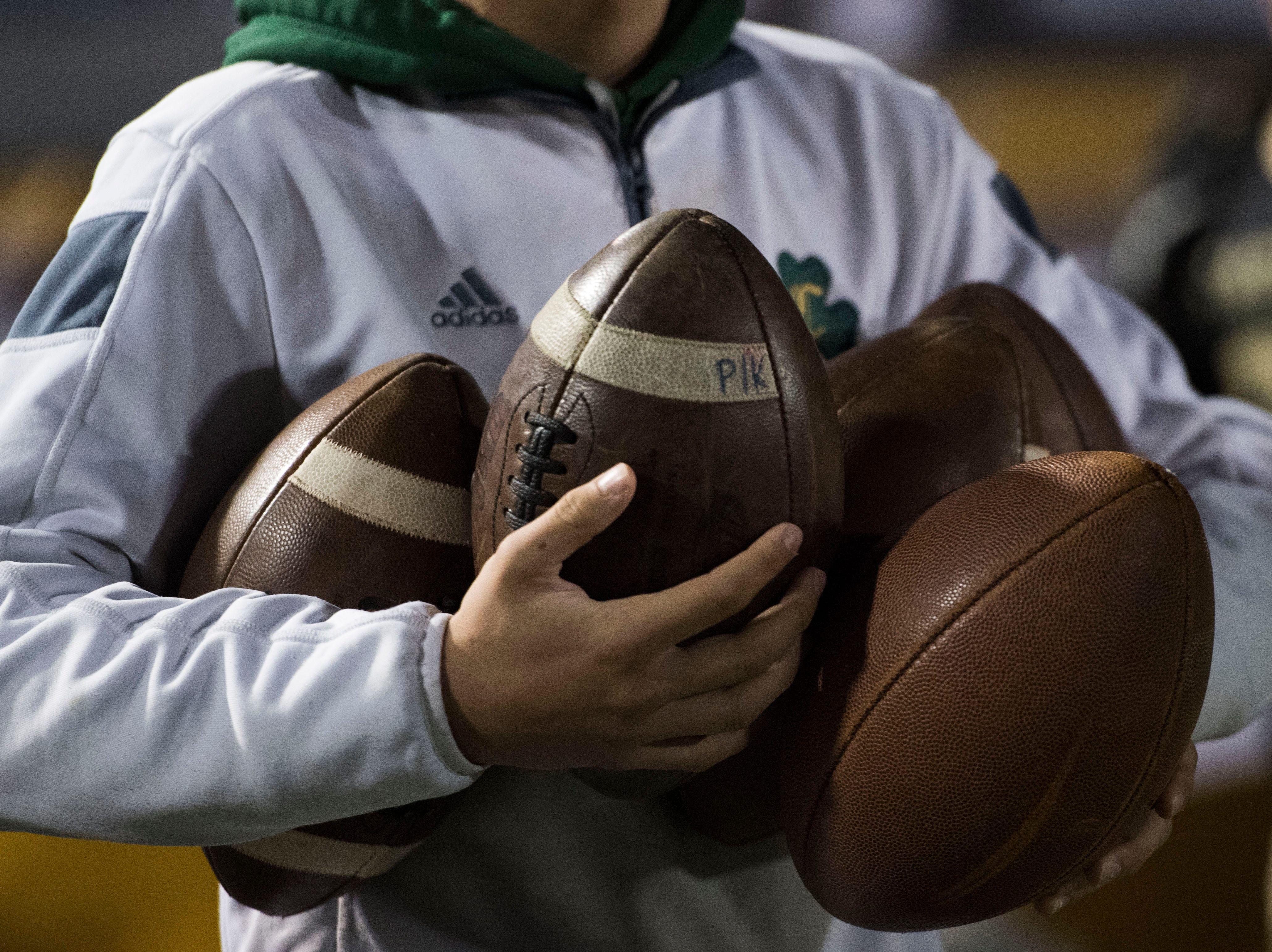 A Catholic ball boy holds multiple balls on the sidelines before a game between Catholic and Central at Catholic Friday, Nov. 23, 2018.