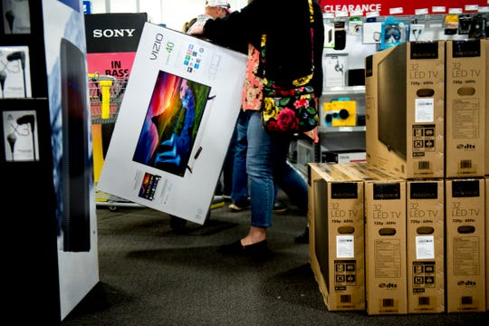 A shopper carries a Vizio television to the checkout during Black Friday shopping at the Turkey Creek Best Buy in West Knoxville on Nov. 22, 2018.