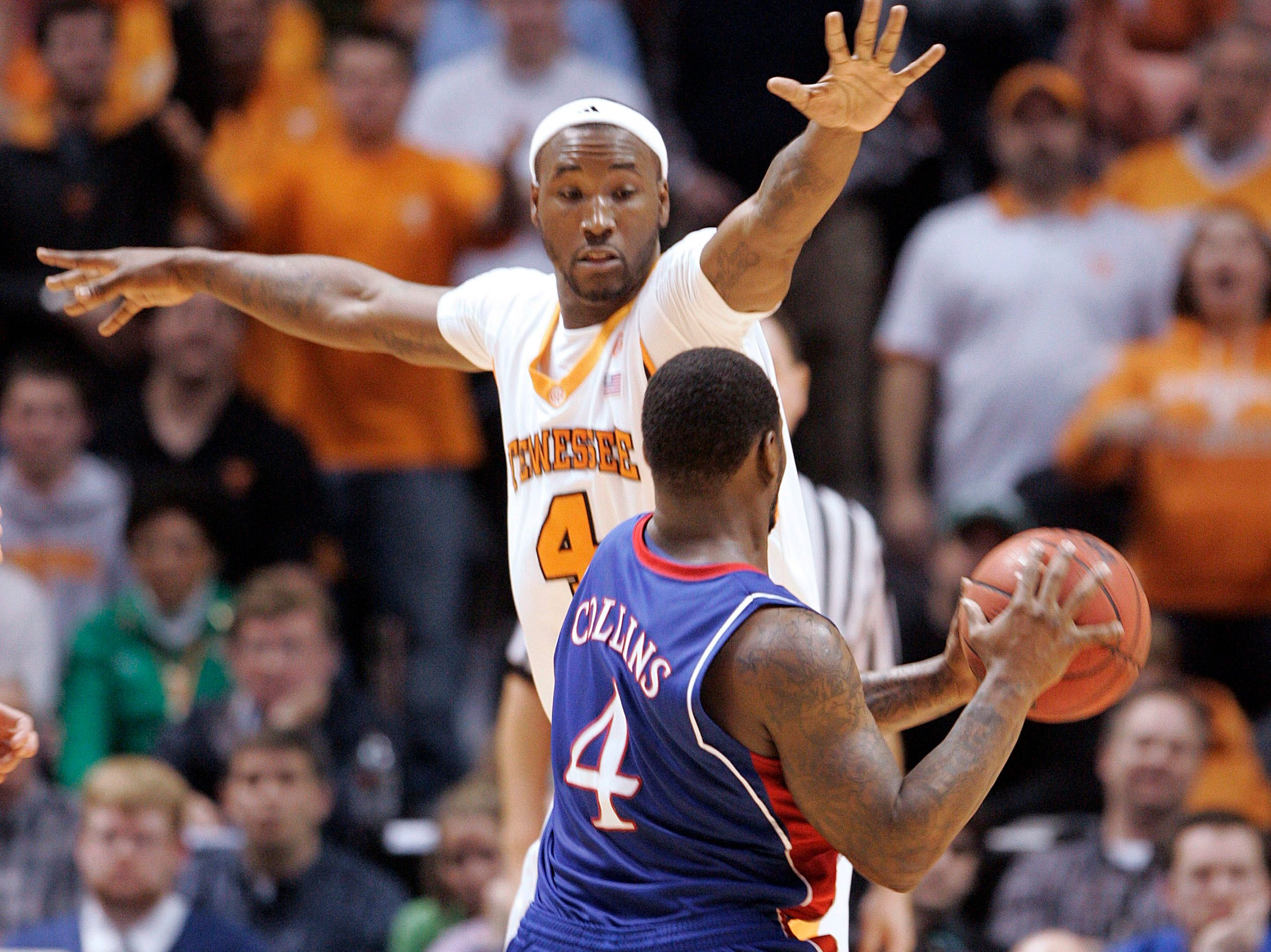 Kansas' Sherron Collins (4) passes the ball while Tennessee's Wayne Chism (4) defends during the second half of an NCAA college basketball game Sunday, Jan. 10, 2010, in Knoxville, Tenn. Tennessee won 76-68.