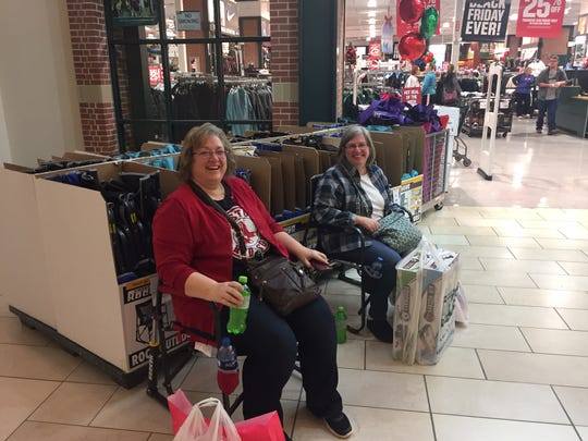 Heidi Streets and Carrie Elder take a break from Black Friday shopping at the River Valley Mall.