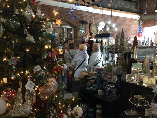 Shoppers check out at Sassafras Gifts in downtown Brighton on Black Friday, Nov. 23, 2018.