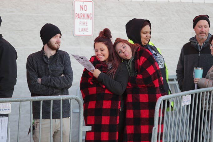 Madi Ohlmann, left, and  Haylee Brunley bundle under a blanket at Best Buy before they opened at 8 a.m. on Black Friday. Nov. 23, 2018