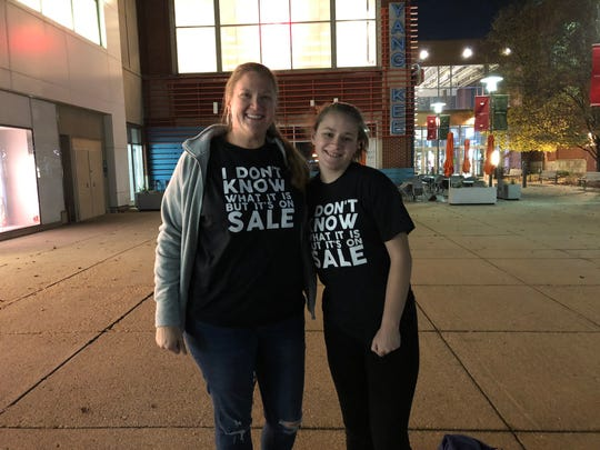 Pam Rice and her daughter Grace show off their Black Friday shirts before dawn at Louisville's Oxmoor Center mall. Nov. 23, 3018