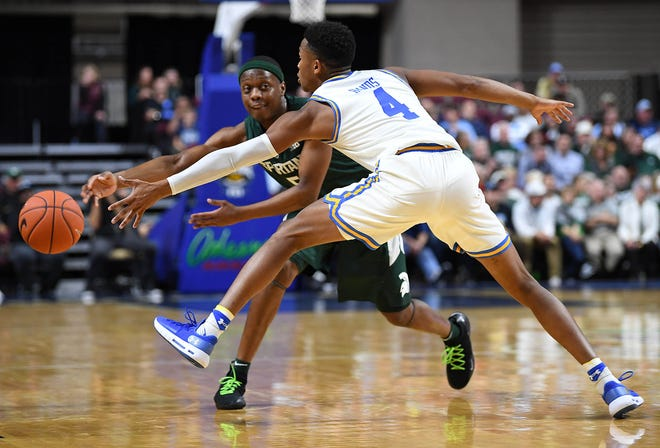 Michigan State junior point guard Cassius Winston passes around junior guard  UCLA guard Jaylen Hands during the first half Thursday at Orleans Arena.