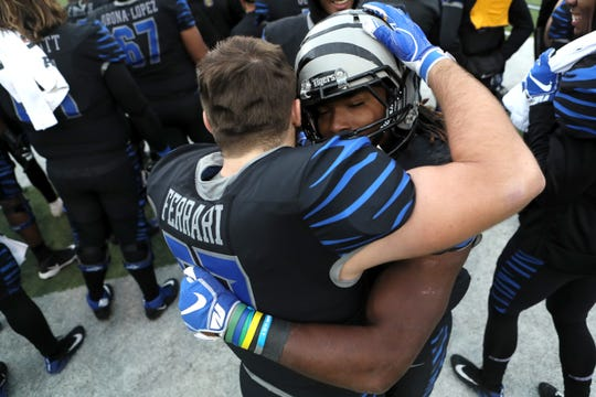 Memphis' Darrell Henderson hugs Hayden Ferrari as the Tigers defeat Houston Cougars to win the AAC West title 52-31 at the Liberty Bowl on Friday, Nov. 23, 2018.