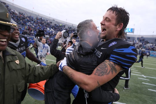 Memphis' Jackson Dillon and Head Coach Mike Norvell embrace as the Tigers defeat Houston Cougars to win the AAC West title 52-31 at the Liberty Bowl on Friday, Nov. 23, 2018.