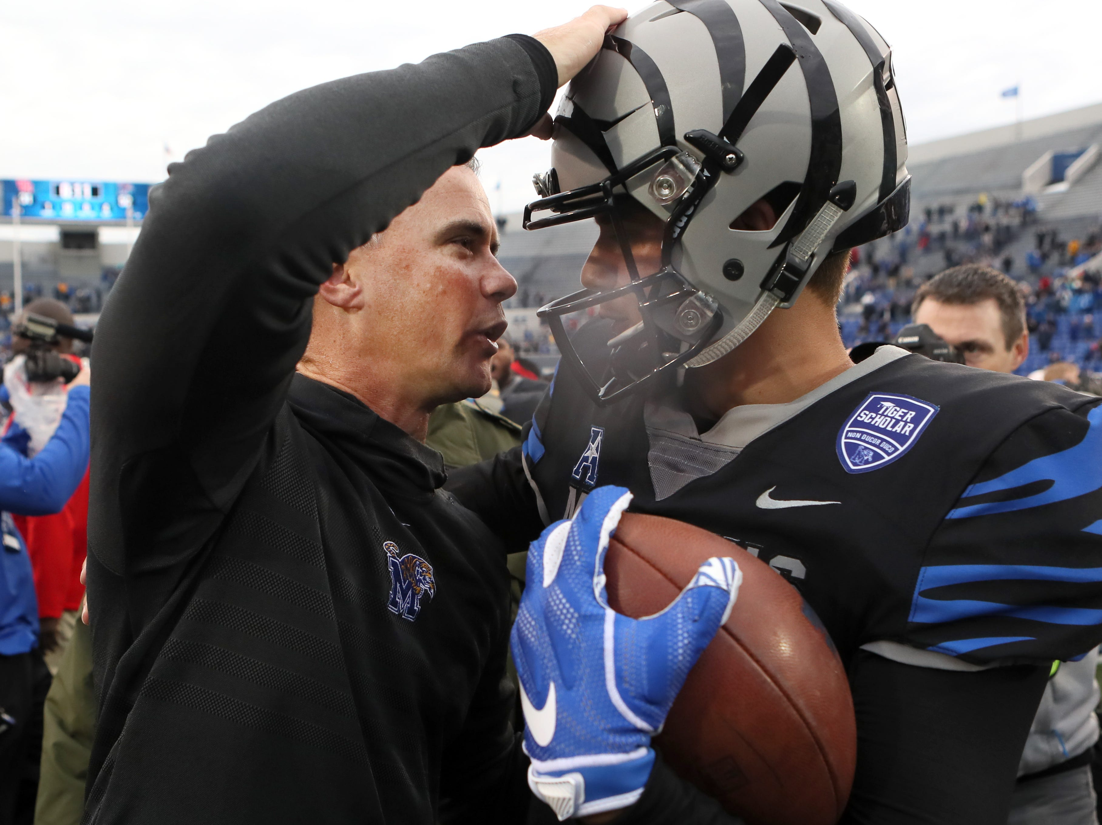Memphis Head Coach Mike Norvell and quarterback Brady White embrace after the Tigers defeat the Houston Cougars to win the AAC West title 52-31 at the Liberty Bowl on Friday, Nov. 23, 2018.
