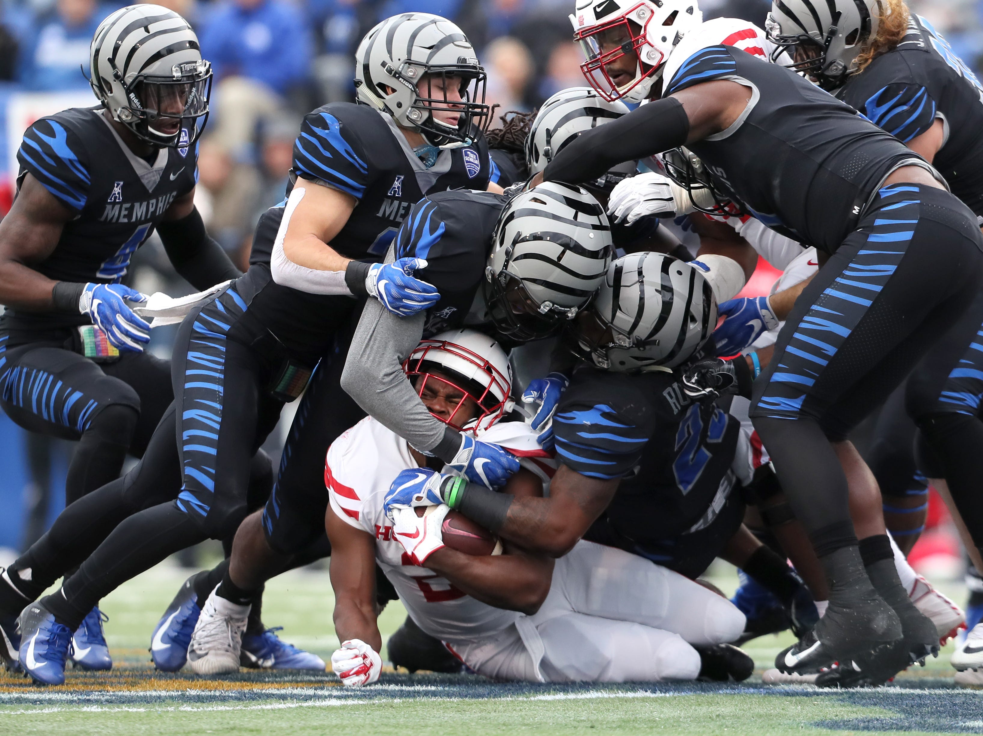 Houston Cougars' Patrick Carr is gang tackled by Memphis Tigers defense, including J.J. Russell (23) at the Liberty Bowl on Friday, Nov. 23, 2018.