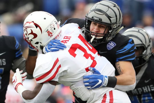 Memphis' Austin Hall tackles Houston Cougars runningback Mulbah Car as the Tigers win the AAC West title 52-31 at the Liberty Bowl on Friday, Nov. 23, 2018.