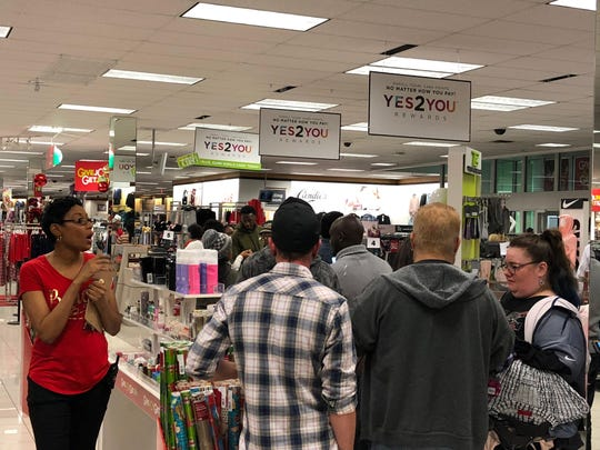 A store representative walks past customers waiting in line at the Kohl's in Cordova on Thanksgiving night.