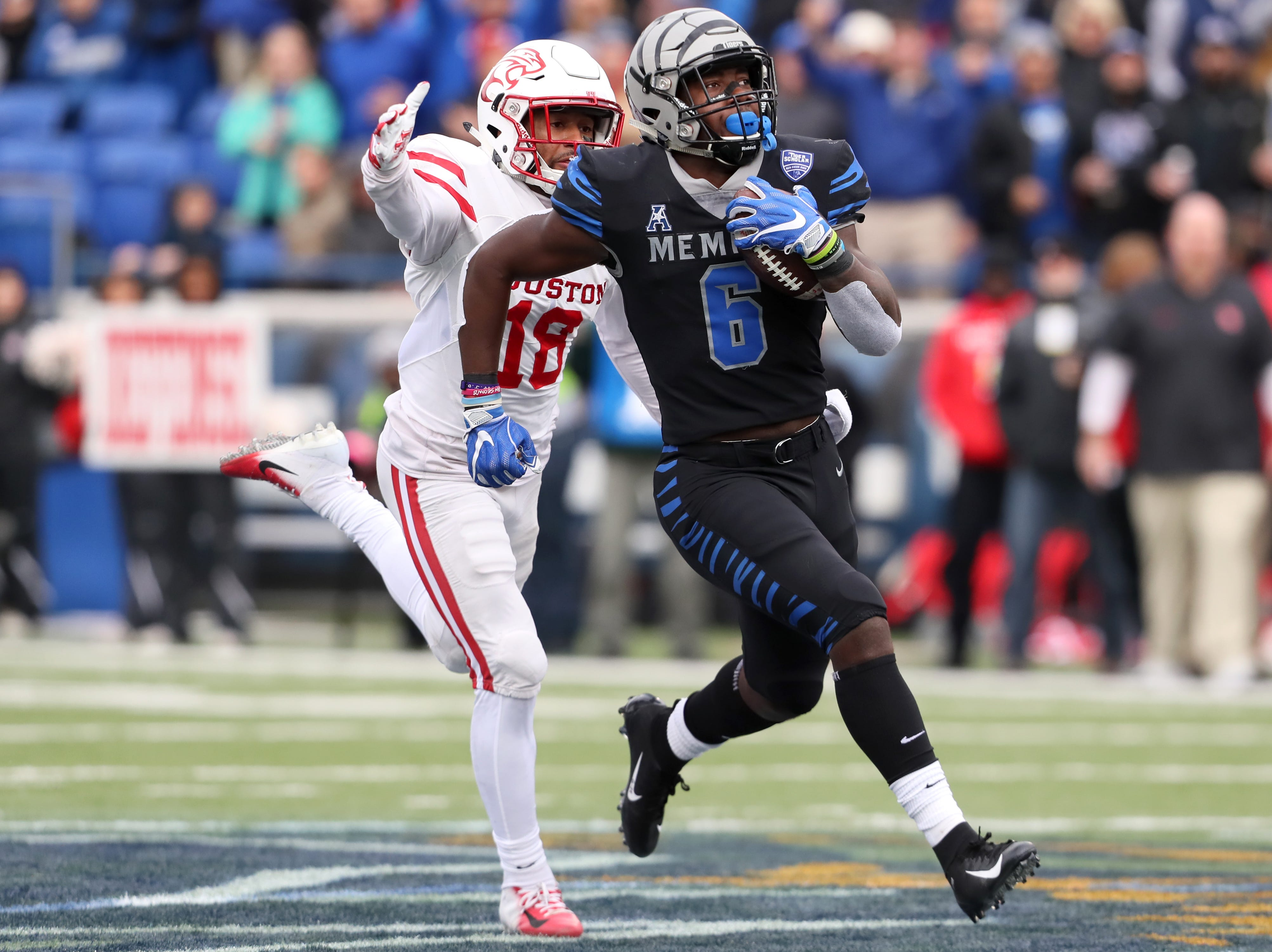 Memphis Tigers' Patrick Taylor Jr. sprints down the field as Houston Cougars defender Alexander Myres chases him down at the Liberty Bowl on Friday, Nov. 23, 2018.